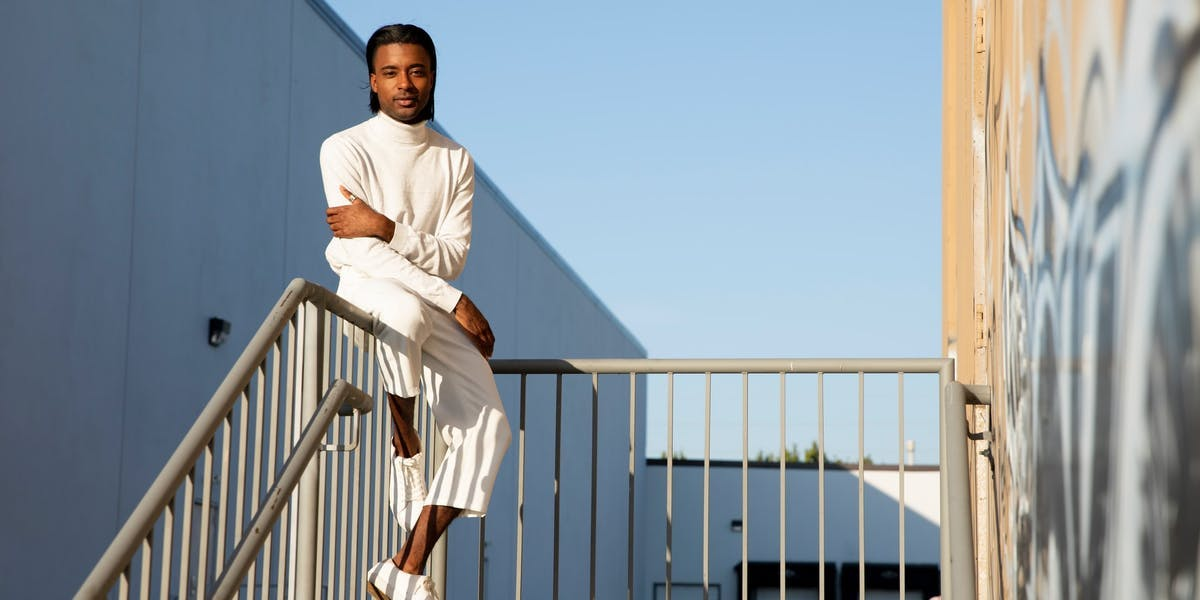 male model sitting on a railing in the sun